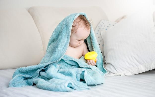 Babyjongen bedekt met blauwe handdoek spelen met gele rubberen eend op de bank na het baden