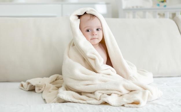 Babyjongen bedekt met grote handdoek na het baden