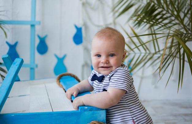 Babyjongen blond met blauwe ogen in een gestreepte jumpsuit staat tegen een muur met een zee-landschap