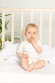 Babyjongen, blondine met blauwe ogen in een witte bodysuit op een bed met katoenen ondergoed thuis voordat hij naar bed gaat, zuigt een vinger