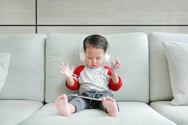 Babyjongen die aan muziek op hoofdtelefoons luisteren
