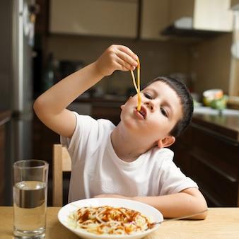 Babyjongen die deegwaren met handen eten