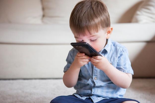 Babyjongen die een telefoon kust. geen ouderlijk toezicht op nieuwe technologieën voor kinderen met smartphones thuis.