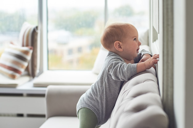 Babyjongen die en op bank tegen groot venster kruipen beklimmen