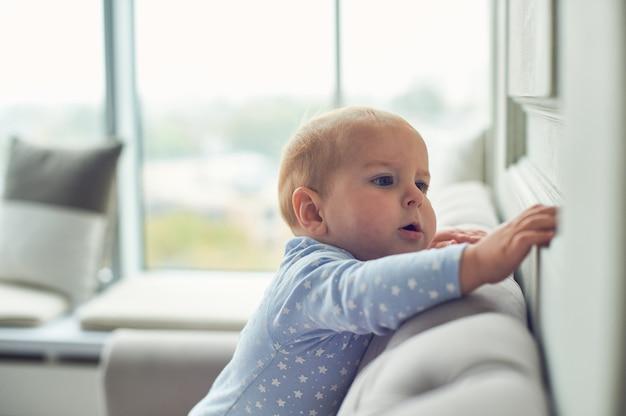 Babyjongen die en op bank thuis kruipen beklimmen