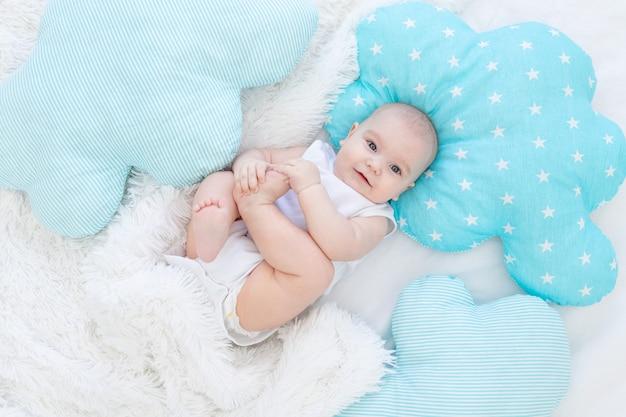 Babyjongen die in bed ligt voordat hij naar bed gaat, schattige, lachende, zes maanden oude, glimlachende kleine baby
