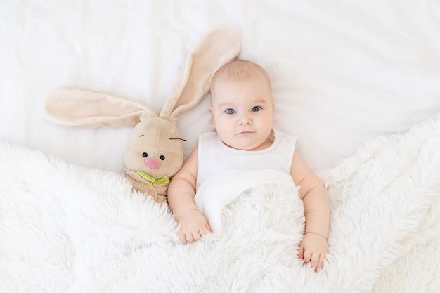 Babyjongen die in een wieg ligt of wakker wordt met een konijnenspeeltje, schattige, grappige zes maanden oude, glimlachende kleine baby
