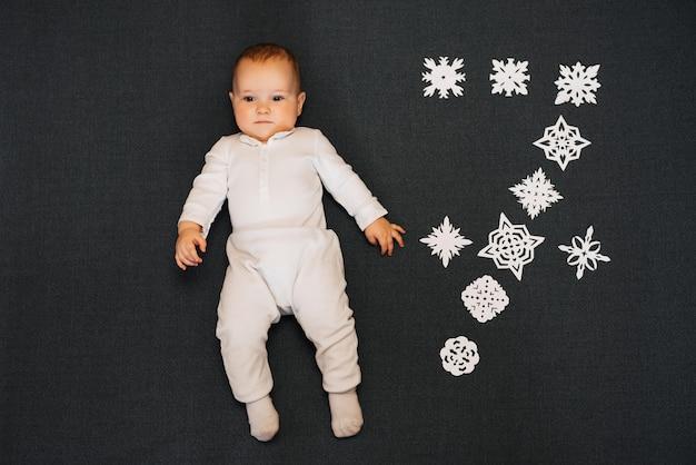 Babyjongen die met eigengemaakte sneeuwvlokken in witte kleren liggen. concept zeven maanden