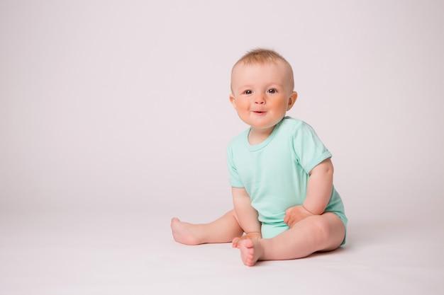 Babyjongen die op wit glimlacht