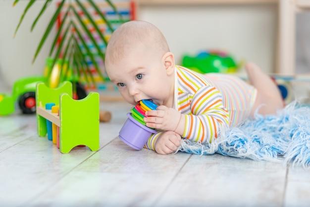 Babyjongen die speelgoed likt of knabbelt in de kinderkamer, schattige kleine baby die op de vloer speelt, ontwikkelings- en speelconcept van kinderen