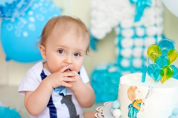 Babyjongen die zijn handen van de verjaardagstaart eet