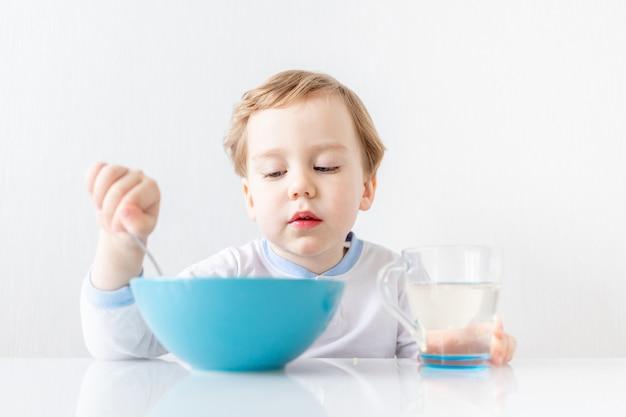 Babyjongen eet thuis met een lepel, het concept van voedsel en voeding voor kinderen