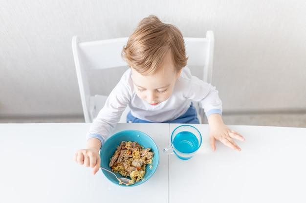 Babyjongen eet thuis met een lepel het concept van voedsel en voeding voor kinderen
