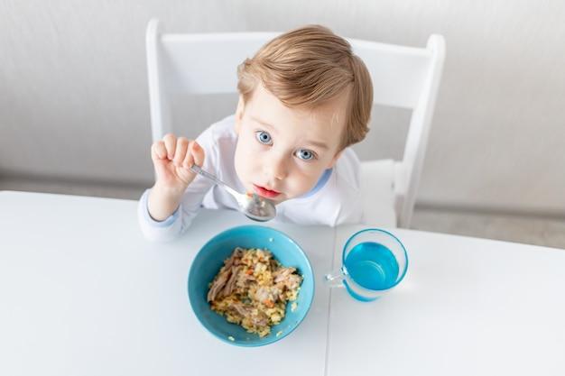 Babyjongen eet thuis met een lepel, het concept van voedsel en voeding voor kinderen.