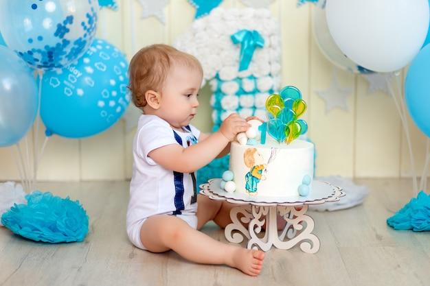 Babyjongen eet zijn cake met zijn handen, baby 1 jaar oud, gelukkige jeugd, verjaardag van kinderen