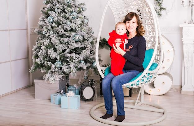 Babyjongen en moeder in de buurt van de kerstboom.