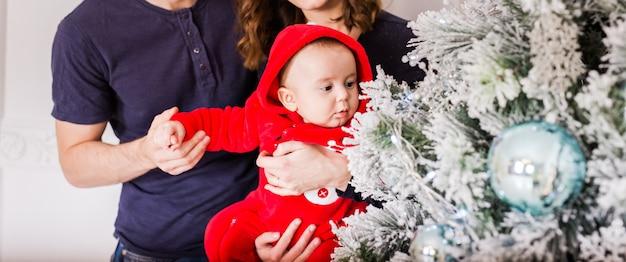 Babyjongen en ouders in de buurt van kerstboom.