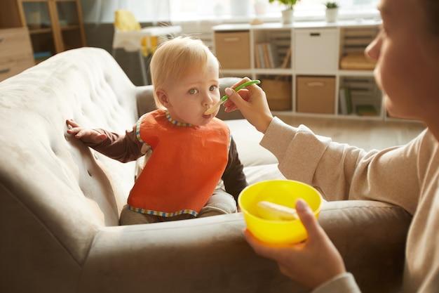 Babyjongen eten met de hulp van zijn moeder tijdens de lunch thuis