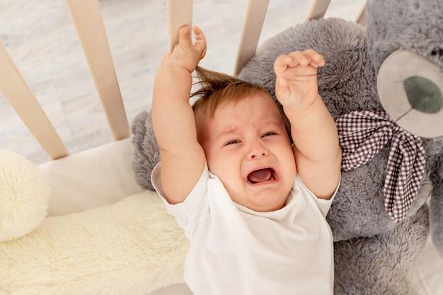 Babyjongen huilend in zijn wieg met een grote teddybeer