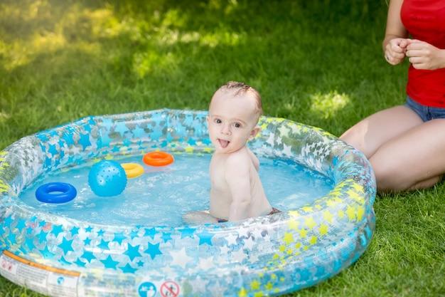 Babyjongen in buitenzwembad spelen met moeder