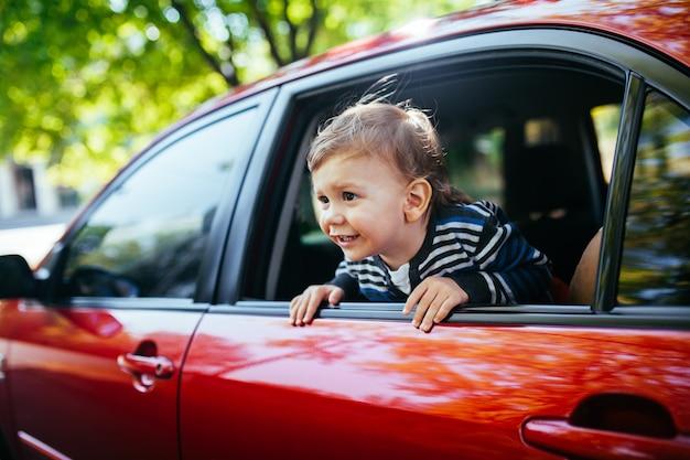 Babyjongen in de auto op zoek naar raam.