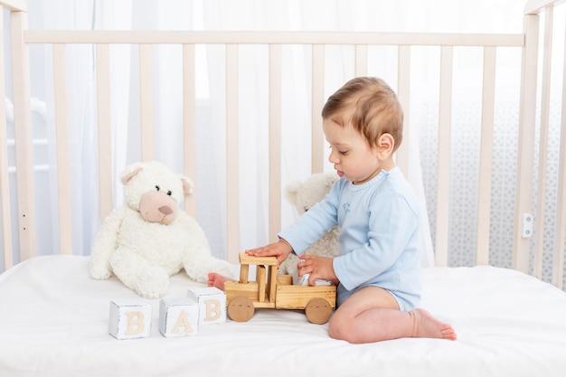 Babyjongen in de wieg in de kinderkamer met houten speelgoed op een katoenen wit bed aan het spelen