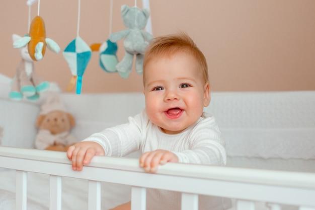 Babyjongen in de wieg in de kinderkamer