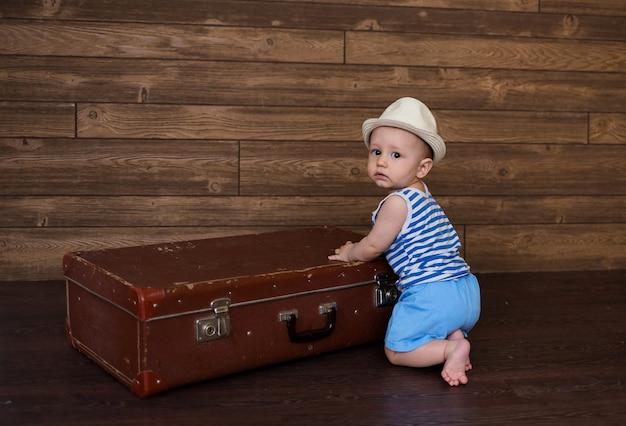 Babyjongen in een gestreept t-shirt en een strooien hoed houdt een retro koffer op een houten bruine ondergrond met ruimte voor tekst