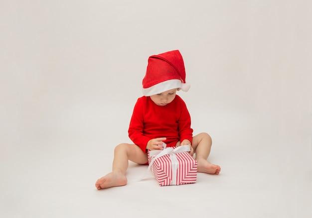 Babyjongen in een kerstmuts opent met een cadeau op een witte geïsoleerde muur