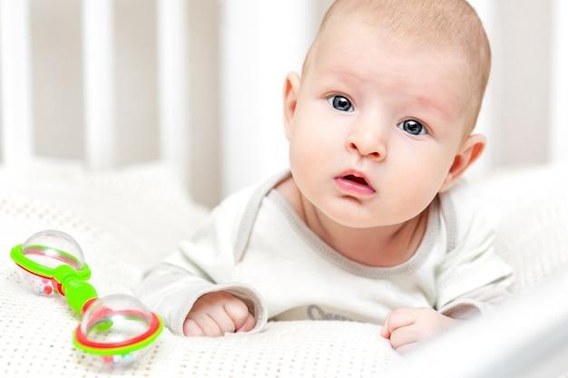 Babyjongen in een voederbak die de camera bekijken.