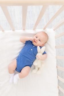Babyjongen in een wieg ligt op zijn rug, een gelukkige pasgeborene wordt wakker