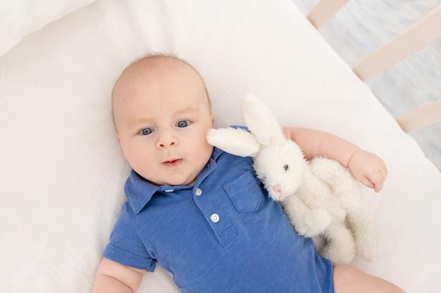 Babyjongen in een wieg ligt op zijn rug met een speeltje, een gelukkige pasgeborene wordt wakker