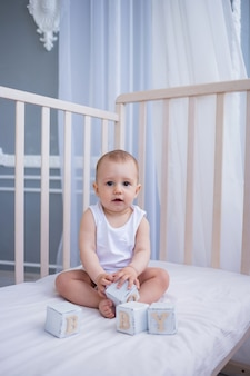 Babyjongen in een witte bodysuit zit in een wieg met een teddybeer en speelt met houten blokjes