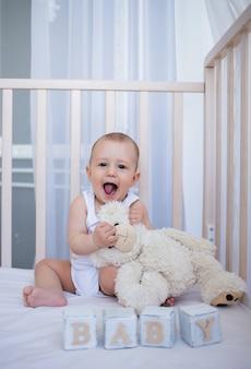 Babyjongen in een witte romper zit met een teddybeer en blokjes met het woord baby in de wieg