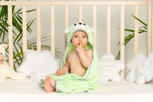 Babyjongen in groene handdoek na bad op bed thuis