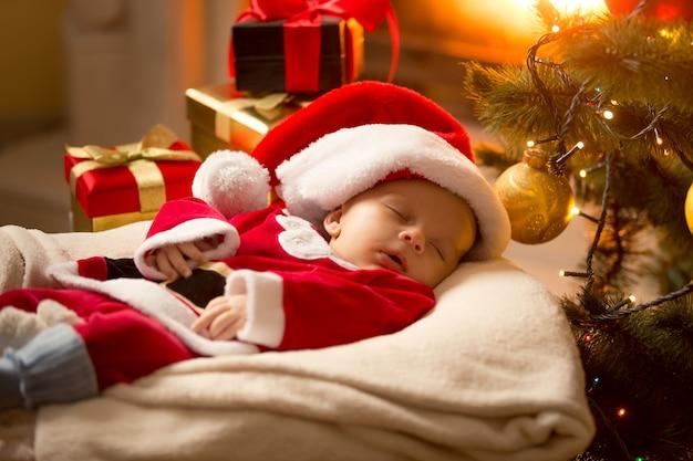 Babyjongen in kerstmankostuum die bij open haard naast kerstboom slaapt