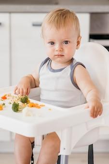 Babyjongen in kinderstoel groenten eten in de keuken