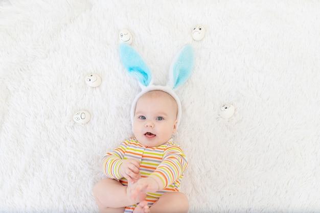 Babyjongen in konijnenoren op zijn hoofd ligt met eieren met emoties, schattige grappige lachende kleine baby. het concept van pasen.