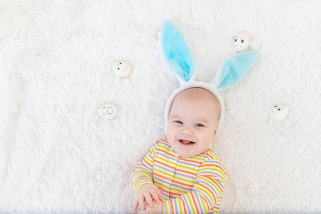 Babyjongen in konijnenoren op zijn hoofd ligt met eieren met emoties, schattige grappige lachende kleine baby.