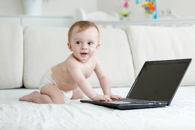 Babyjongen in luiers kruipen op bed en het gebruik van laptop com