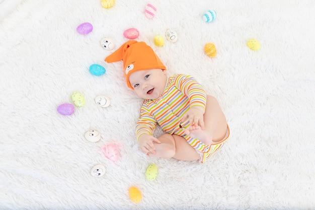 Babyjongen in oranje kleren die met paaseieren liggen, leuke grappige glimlachende kleine baby. het concept van pasen.