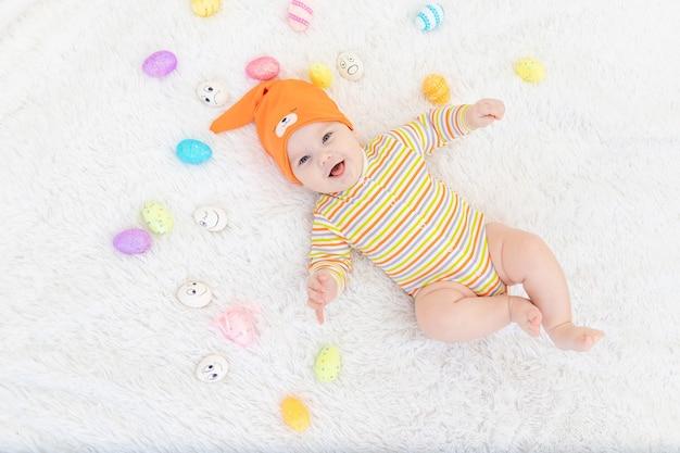 Babyjongen in oranje kleren liggen met paaseieren, leuke grappige glimlachende kleine baby.