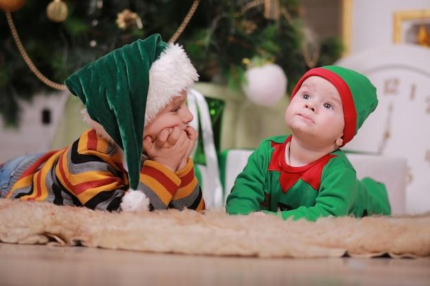 Babyjongen in rood groen elf kostuum met zijn oudere broer in kerstmuts, zittend onder de kerstboom en geschenkdozen.