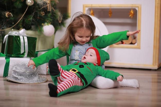 Babyjongen in rood groen elf kostuum met zijn oudere zus zitten en plezier maken onder de kerstboom met geschenkdozen.