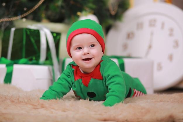 Babyjongen in rood groen elf kostuum zittend onder kerstboom en geschenkdozen.