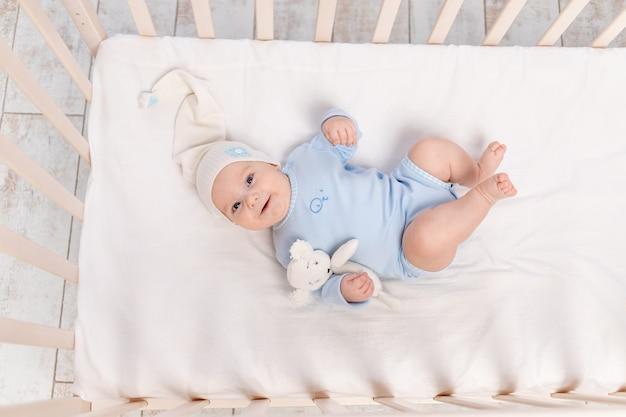 Babyjongen in wieg met teddybeer speelgoed gaat naar bed of werd wakker in de ochtend, familie en geboorte concept