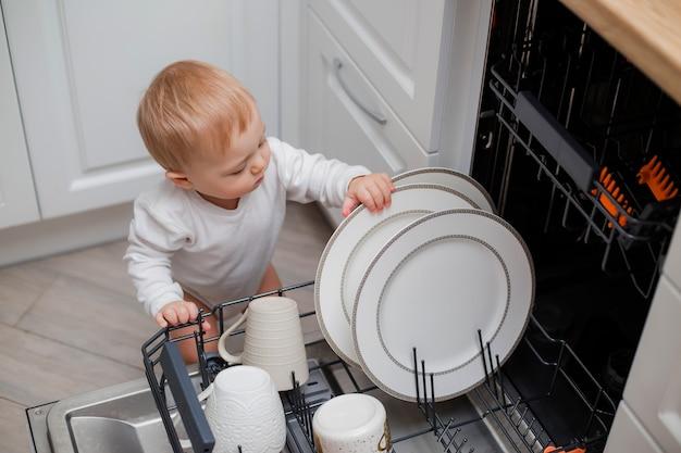 Babyjongen in witte kleren gebruikt vaatwasser