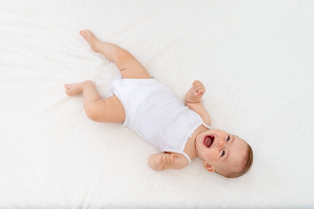 Babyjongen in witte kleren, zittend in een wieg