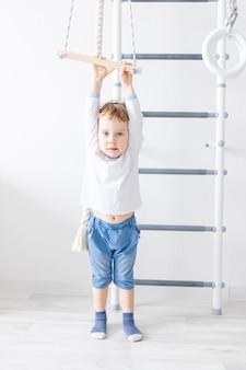 Babyjongen klimt op de zweedse muur van het huis