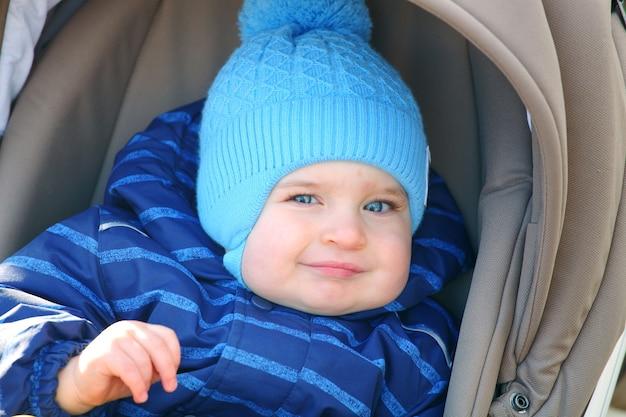 Babyjongen liggend in een wandelwagen en glimlachen